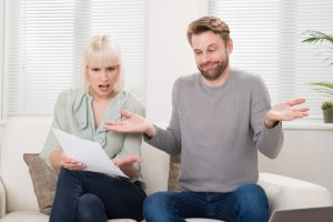 Shocked Young Couple Sitting On Sofa Looking At Bill At Home